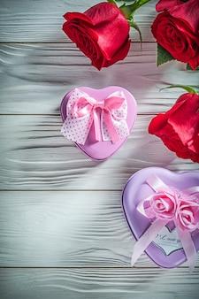 Pudełka metalowe w kształcie serca z naturalnymi czerwonymi różami na drewnianej desce
