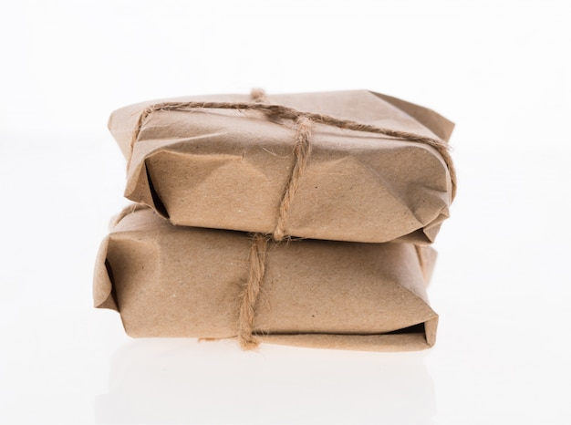Pudełka na paczki owinięte papierem makulaturowym i związane liną jutową na białym tle