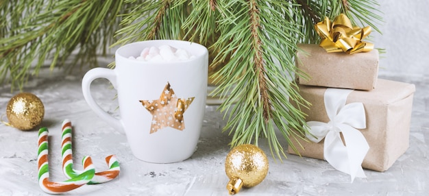 Pudełka na prezenty, gorący napój z marshmallows, laski cukierków i złote kule na odrapanym szarym