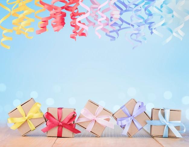 Pudełka na prezenty i wielokolorowa serpentyna na niebieskim tle. tło wakacje