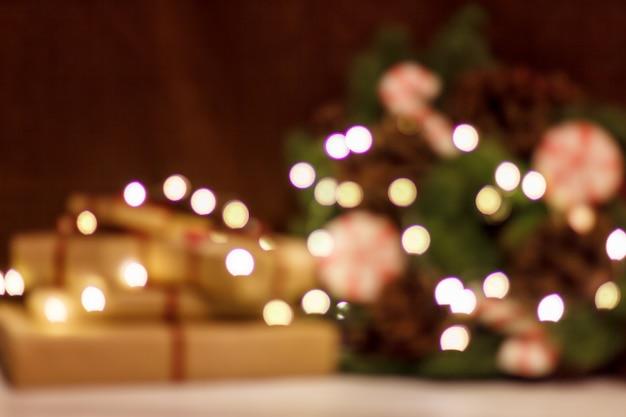 Pudełka na prezenty i wieniec świąteczny ze świecącą girlandą. zamazany tło bez ostrości z bokeh