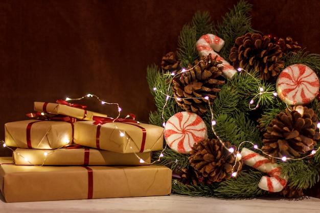Pudełka na prezenty i wieniec świąteczny ze świecącą girlandą.
