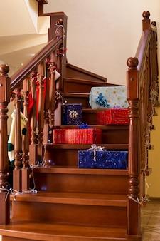Pudełka na prezenty leżące na schodach kilka świątecznych prezentów na schodach czekających na otwarcie niespodzianek dla ...