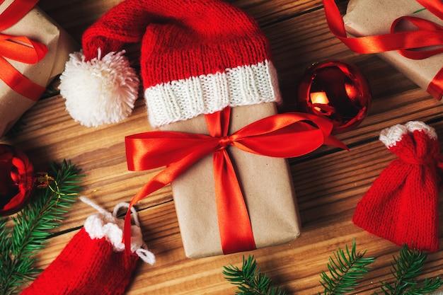 Pudełka na prezenty na boże narodzenie. czerwona wstążka, bombki i gałęzie drzew