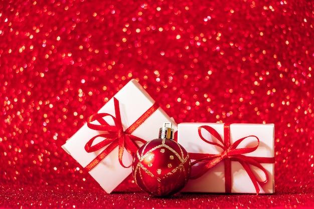 Pudełka na prezenty na czerwonym tle błyszczące. koncepcja bożego narodzenia, miejsce na tekst.