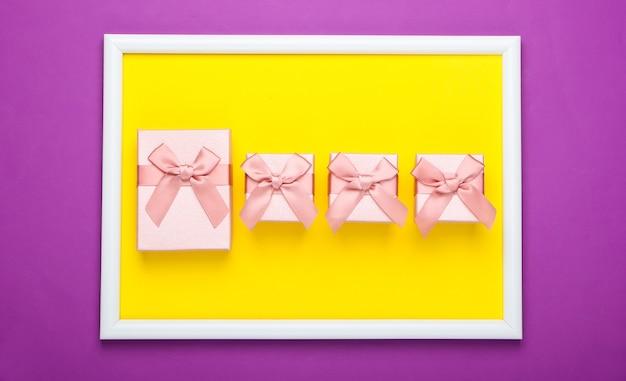 Pudełka na prezenty na fioletowej powierzchni z ramką na zdjęcia