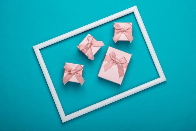 Pudełka na prezenty na niebieskiej powierzchni z białą ramką