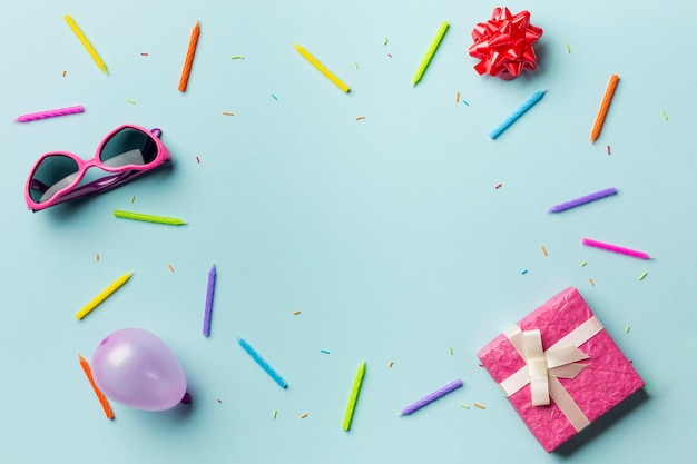 Pudełka na prezenty; okulary słoneczne; kokardka ze wstążką; balon; kolorowe świece i kropi na niebieskim tle