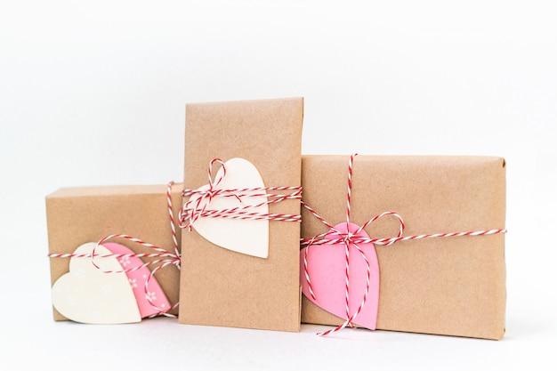 Pudełka na prezenty owinięte w papier rzemieślniczy i ozdobione czerwoną wstążką i drewnianymi sercami