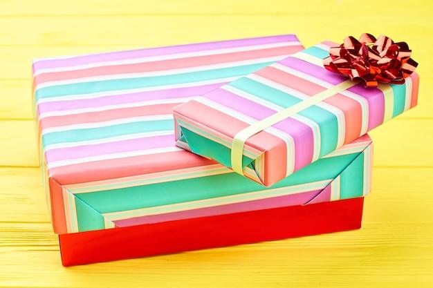 Pudełka na prezenty świąteczne i czerwona kokarda.