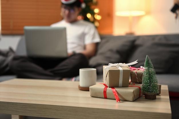 Pudełka na prezenty świąteczne i filiżankę kawy na drewnianym stole w salonie.