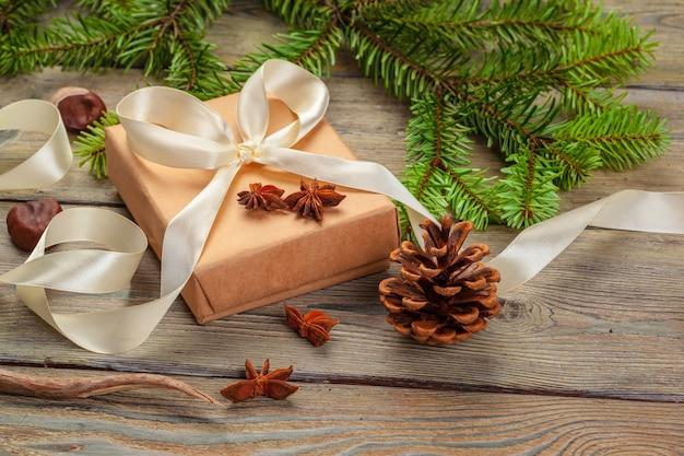 Pudełka na prezenty świąteczne i gałąź jodła na drewnianym stole.
