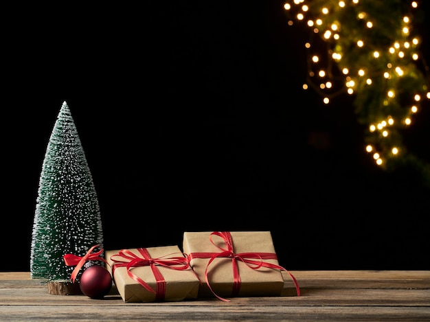 Pudełka na prezenty świąteczne i jodła na drewnianym stole przed niewyraźne świąteczne światła, miejsce na tekst