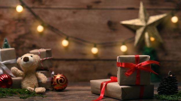 Pudełka na prezenty świąteczne i misia na drewnianym stole.