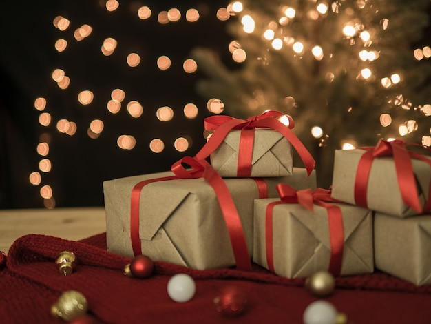 Pudełka na prezenty świąteczne i piłka na stole z lampkami bokeh.