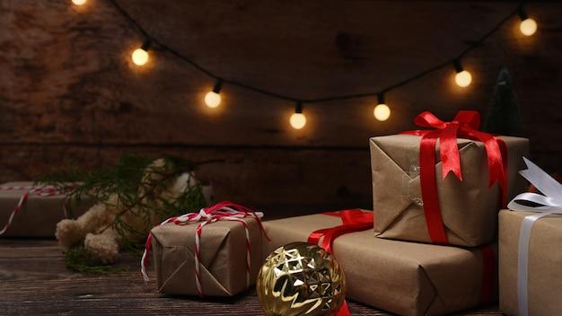 Pudełka na prezenty świąteczne, misia i gałęzie sosny na drewnianym stole.