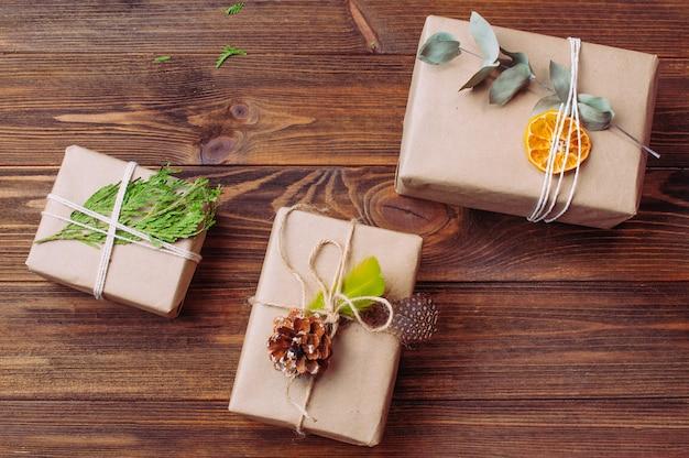 Pudełka na prezenty świąteczne ozdobione naturalnymi detalami na rustykalnej drewnianej powierzchni. przyjazny dla środowiska, ręcznie robiony, świąteczny wystrój koncepcji. widok z góry, płaski układ.