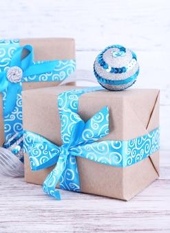 Pudełka na prezenty świąteczne ozdobione niebieską wstążką na stole na drewnianej powierzchni ściany