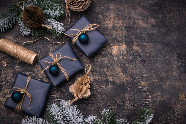 Pudełka na prezenty świąteczne w niebieskim papierze na ciemnym drewnianym stole