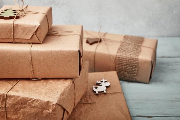 Pudełka na prezenty świąteczne zawinięte w papier pakowy na niebieskim drewnianym stole.