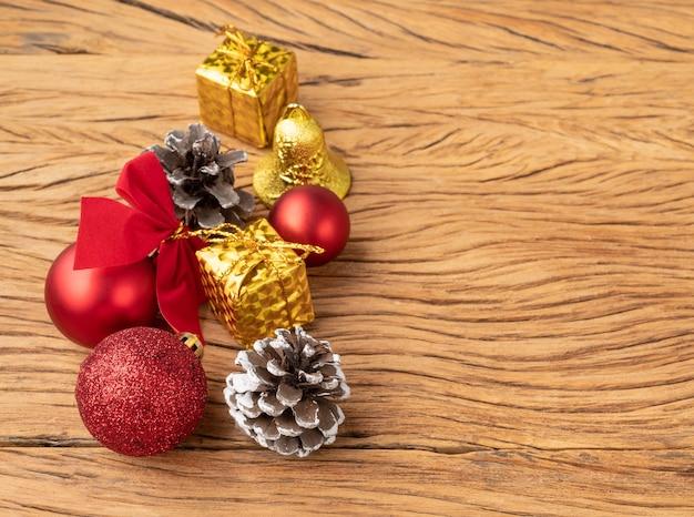Pudełka na prezenty, szyszki, bombki i łuk nad drewnianym stołem. różne świąteczne dekoracje z miejsca na kopię.
