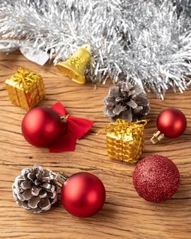 Pudełka na prezenty, szyszki, bombki i łuk nad drewnianym stołem. różne świąteczne dekoracje.