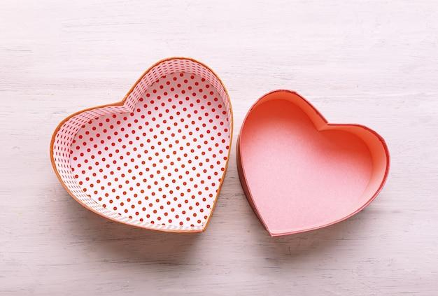 Pudełka na prezenty w kształcie serca na jasnym drewnianym stole