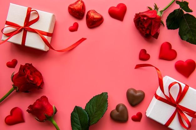 Pudełka na prezenty z czerwoną wstążką i czerwonymi różami na walentynki
