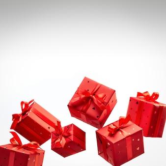 Pudełka na prezenty z czerwonego papieru przewiązane atłasowymi wstążkami z kokardkami