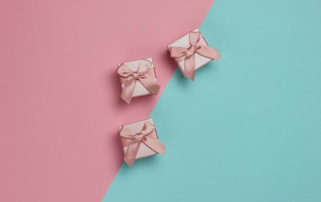 Pudełka na prezenty z kokardą na pastelowym tle niebiesko-różowym. kompozycja na boże narodzenie, urodziny lub wesele. widok z góry