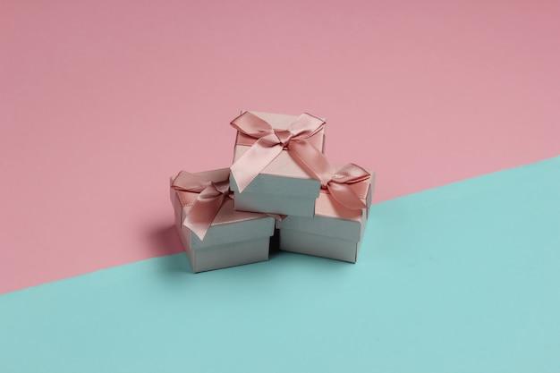 Pudełka na prezenty z kokardą na pastelowym tle niebiesko-różowym. kompozycja na boże narodzenie, urodziny lub wesele.