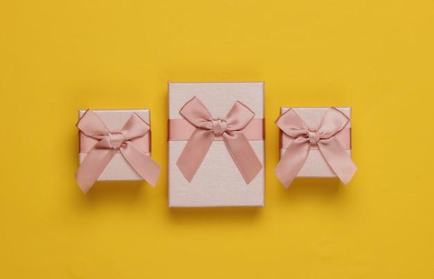 Pudełka na prezenty z kokardą na żółtym tle. kompozycja na boże narodzenie, urodziny lub wesele. widok z góry