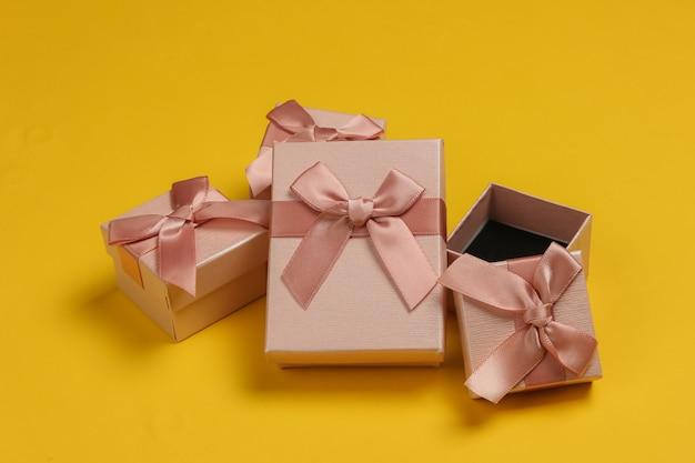Pudełka na prezenty z kokardą na żółtym tle. kompozycja na boże narodzenie, urodziny lub wesele.