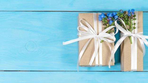 Pudełka na prezenty z kwiatami na niebieskim tle.