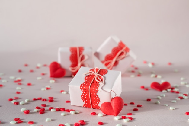Pudełka na prezenty z prezentami i dekoracjami na walentynki. na różowym tle z posypką.