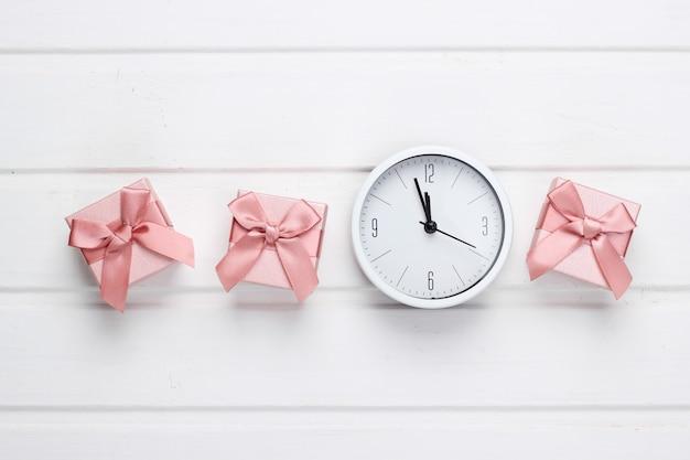 Pudełka na prezenty z zegarem na białej powierzchni drewnianej. widok z góry