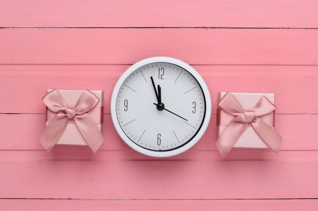 Pudełka Na Prezenty Z Zegarem Na Różowej Powierzchni Drewnianej. Widok Z Góry Premium Zdjęcia