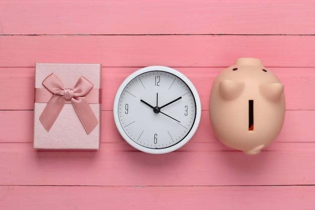 Pudełka na prezenty z zegarem, skarbonka na różowej powierzchni drewnianej. widok z góry