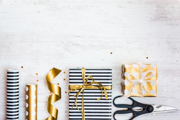 Pudełka na prezenty zapakowane w czarno-białe paski i papier w złote kropki oraz materiały do pakowania