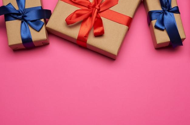 Pudełka na prezenty zawinięte w brązowy papier i przewiązane czerwono-niebieską kokardką, prezenty na różowym tle, miejsce na tekst
