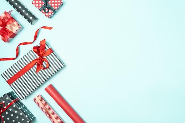 Pudełka na prezenty zawinięte w czarno-białe paski i czerwony papier z materiałami do pakowania na niebieskim tle. przygotowanie prezentów świątecznych.