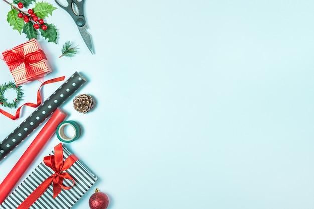 Pudełka na prezenty zawinięte w czarno-białe paski, kropkowany i czerwony papier oraz materiały do pakowania na niebieskim tle. przygotowanie prezentów świątecznych.
