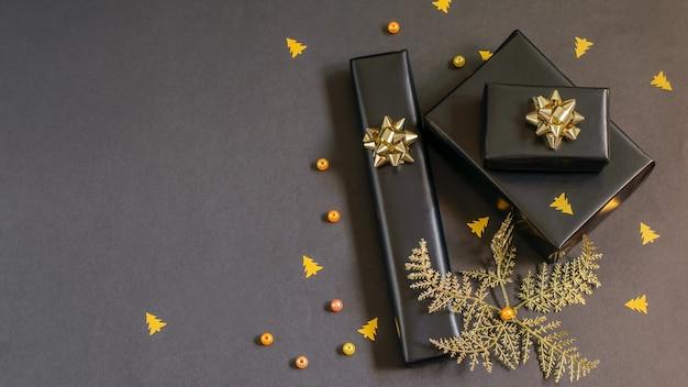 Pudełka na prezenty zawinięte w czarny świąteczny papier ze złotymi bombkami, koralikami i confetii. ręcznie robione prezenty świąteczne, koncepcje diy.