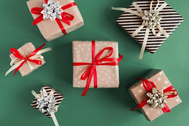 Pudełka na prezenty zawinięte w papier pakowy na zielonym tle. prezenty świąteczne do samodzielnego pakowania