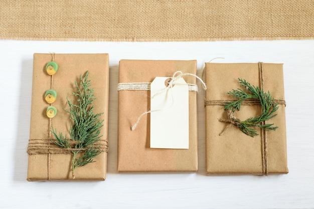 Pudełka na prezenty zawinięte w papier rzemieślniczy i zawiązane na supeł, świątecznie udekorowane.