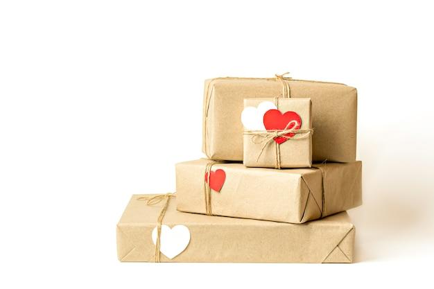 Pudełka na prezenty zawinięte w papier rzemieślniczy z recyklingu, przewiązane sznurkiem na białym tle