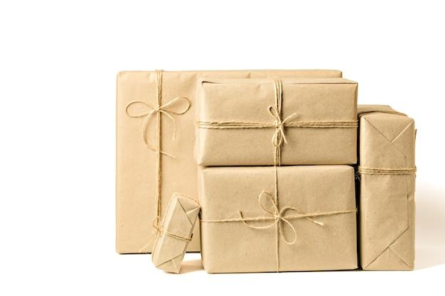 Pudełka na prezenty zawinięte w papier rzemieślniczy z recyklingu związany sznurkiem na białym tle