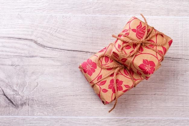 Pudełka owinięte papierem prezentowym. prezentuj pudełka z kokardą ze sznurka. przygotuj prezenty dla ukochanych osób. szczęście dookoła.