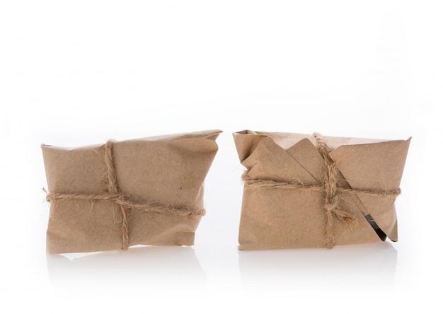 Pudełka paczek owinięte papierem z recyklingu i związane liną jutową na białym tle