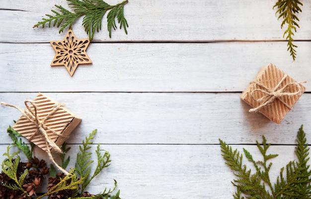 Pudełka papierowe i zielone gałęzie na białym drewnianym tle